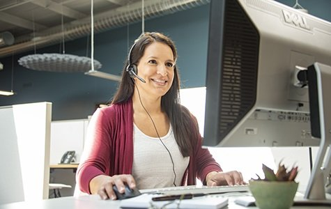 Female compliance specialist on phone and computer